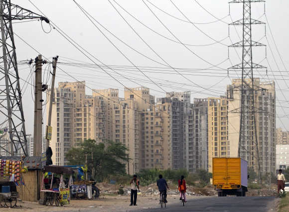 People ride their bicycles under overhead power cables, against the backdrop of multi-storey residential apartments.