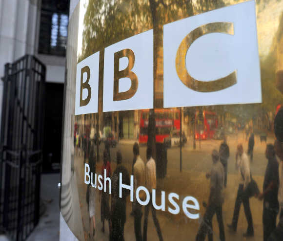 People are reflected in a sign as they walk past British Broadcasting Corporation offices in central London.