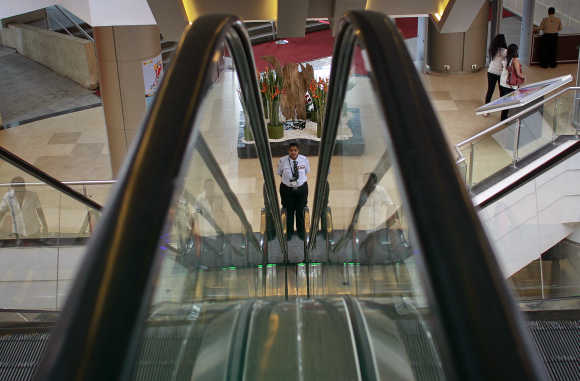A private security personnel stands guard between escalators inside a shopping mall in Mumbai.