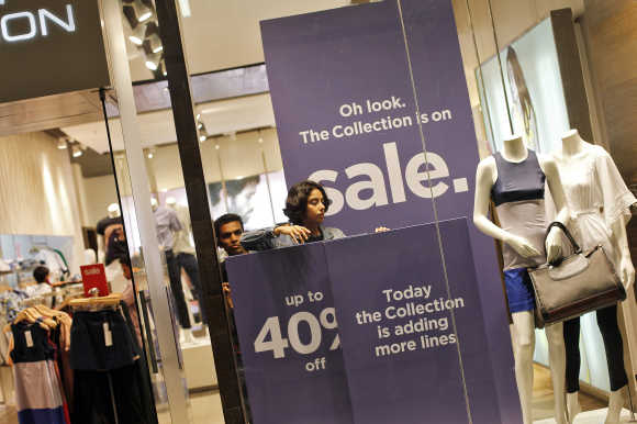 An employee adjusts the window display at a retail store inside a shopping mall in Mumbai.