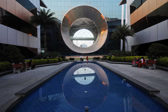 Employees walk in front of a building dubbed the 'washing machine', a well-known landmark built by Infosys at the Electronics City IT district in Bangalore.