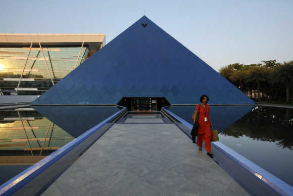 An employee walks out of an iconic pyramid-shaped building made out of glass in the Infosys campus at Electronics City in Bangalore.
