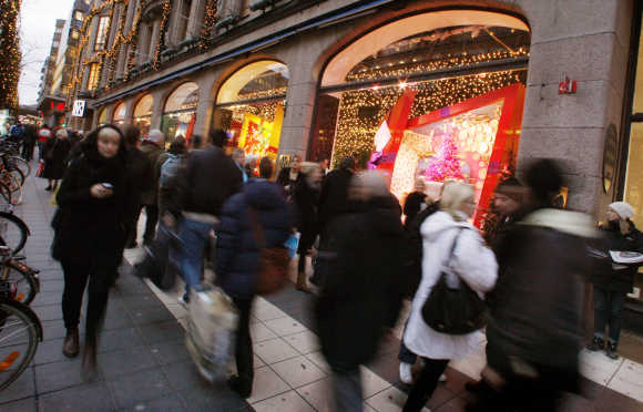 People walk past Christmas window displays at a department store in Stockholm.