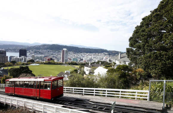 The Wellington Cable Car is seen ascending with a view of the city in the background.
