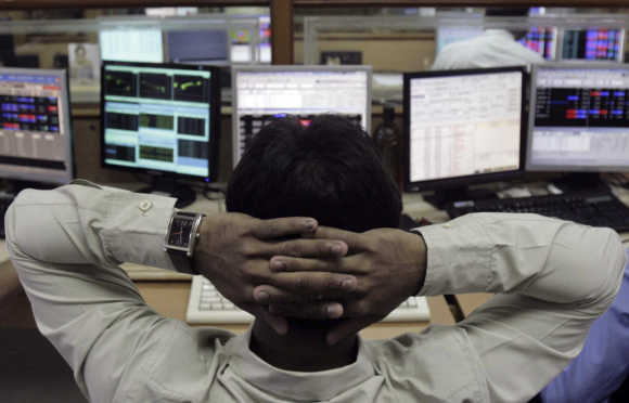 A broker monitors share prices at a brokerage firm in Mumbai.