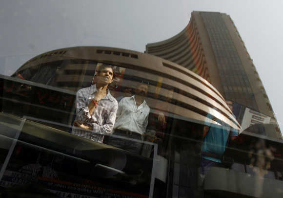 BSE building is reflected on a glass window as people look at a large screen displaying India's benchmark share index in Mumbai.