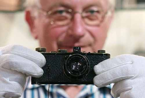 A former employee of a Leica shop Rupert Eder poses with a Leica 0 series camera in Westlicht gallery in Vienna.