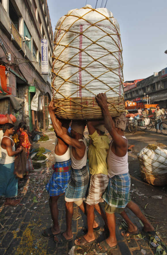Workers carry a packed basket of vegetables at a wholesale market in Kolkata.