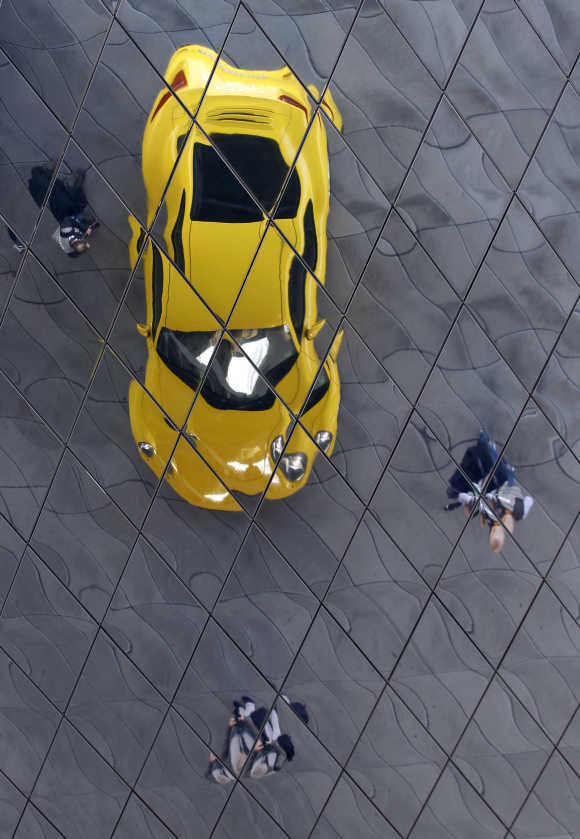 Porsche 911 sports car is reflected in a roof at the Porsche factory in Stuttgart, Germany.