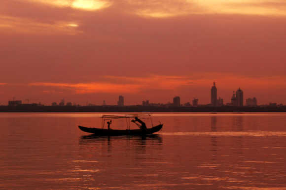 A boat plys the water of East Lake at sunset in the central Chinese city of Wuhan.