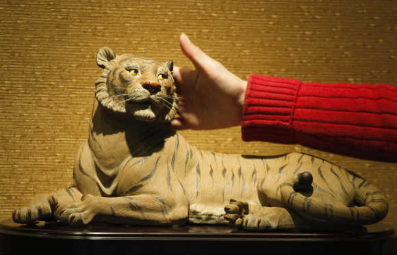 Worker introduces a ceramic tiger to visitors at an exhibition hall of Xinshiwan ceramic factory in Foshan, Guangdong province, China.