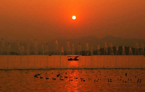 A fishing boat is seen at sunset on the West Lake in Hangzhou, capital city of east China's Zhejiang Province.