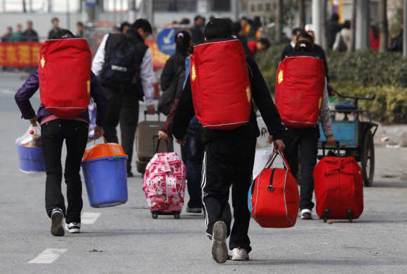 Migrant workers carrying their luggage walk to the Dongguan East train station in China