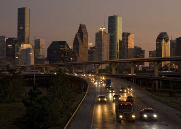Traffic flows at dusk with the downtown Houston skyline in the background as night falls.