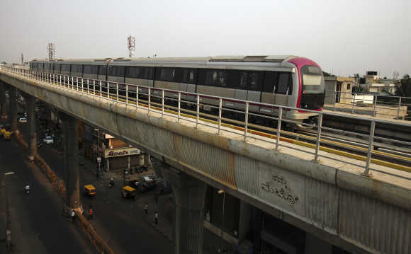 Metro train travels along an elevated track as traffic passes below in the Indira Nagar area of Bangalore.