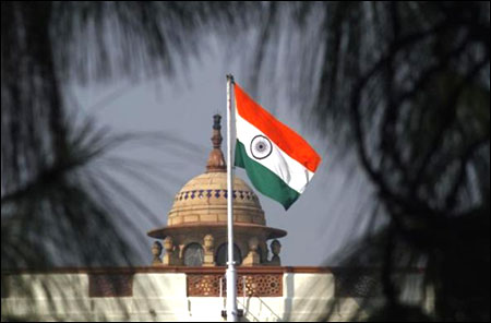 An Indian national flag flutters on top of the parliament building.