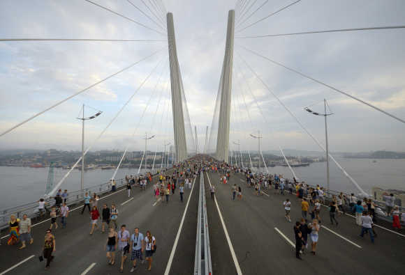 People walk on the bridge across the Golden Horn bay after its opening in Vladivostok, Russia.