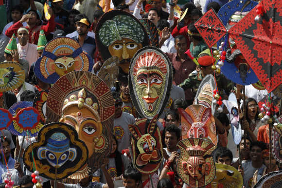 People carry masks during a rally to celebrate Pohela Boishakh, the first day of Bengali new year, in Dhaka.
