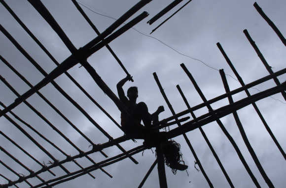 A man is silhouetted against the sky while sitting on wooden scaffolding, as he constructs a temporary tent in Mumbai.