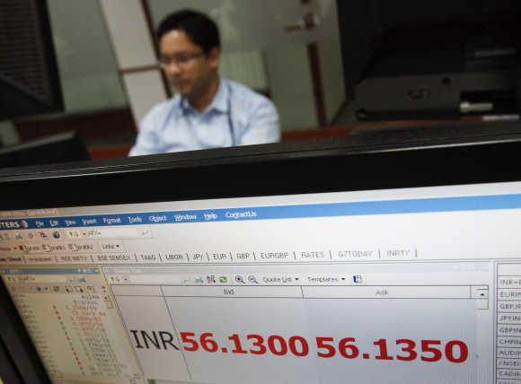 A foreign exchange trader works as the exchange rate of the Indian rupee to US dollar is displayed on a screen at a trading firm in Mumbai.