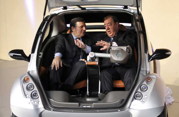 European Commission President Jose Manuel Barroso, left, and Jesus Echabe, right, President of Hiriko, inside the car at the EU headquarters in Brussels.