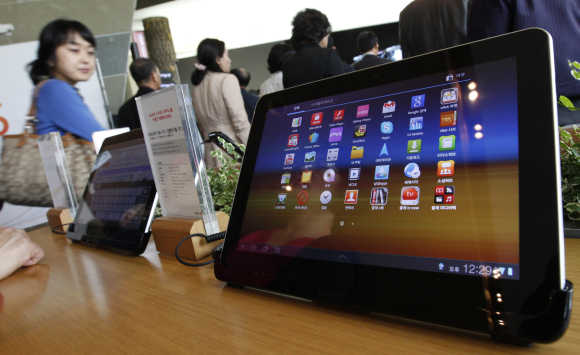Visitors walk past Samsung Electronics' Galaxy Tab 10.1 tablets on display in Seoul.