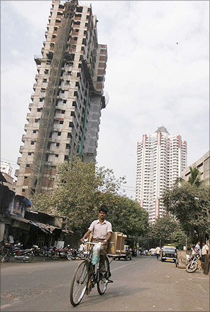 A man cycles past newly constructed buildings.