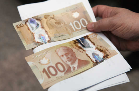 A man holds Canadian dollar notes in Toronto.
