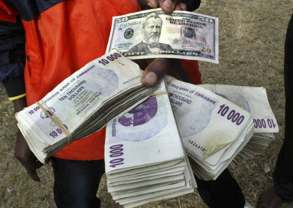 A black market currency trader shows off US and Zimbabwean bank notes in the capital Harare.