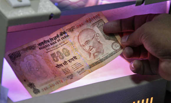 An employee uses an electronic machine to check a currency note inside a bank in Allahabad.