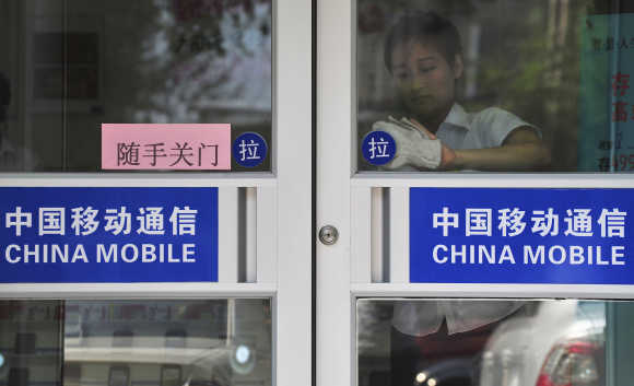 A worker cleans the door of a China Mobile branch in Shenyang, China.