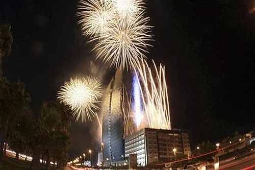 Fireworks explode above a giant video screen in Jeddah