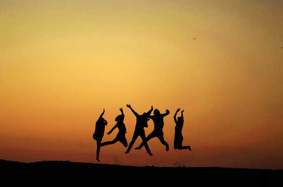 People jump off a sand bank in Venice, Los Angeles, California.