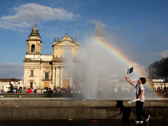 A child plays near a fountain at the Parque Central in Guatemala City.