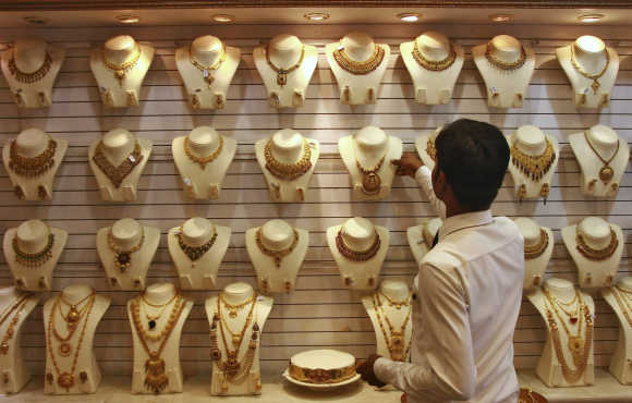 A salesman arranges a gold necklace inside a jewellery showroom in Kochi.
