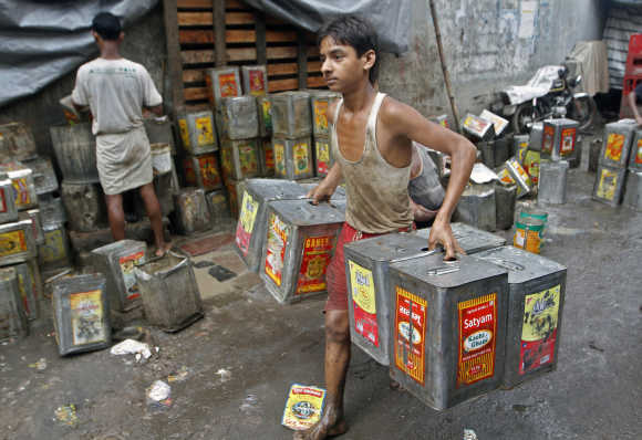 A boy carries recycled mustard oil tin containers from a roadside workshop in Kolkata.
