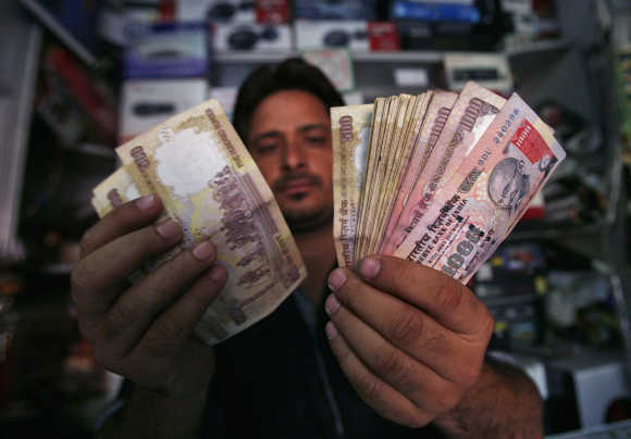 A shopkeeper poses for a picture as he counts notes at his shop in Jammu.