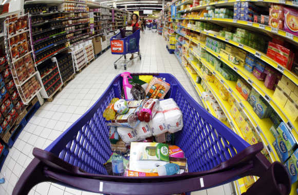 A shopping trolley with food sits parked in an aisle as customers shop at a supermarket in Nice, France.