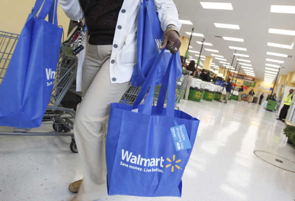 A shopper carries her purchases from Walmart Neighborhood Market in Chicago.