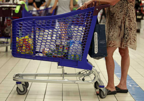 A customer pushes a shopping trolley down an aisle at Carrefour Planet supermarket in Nice, France.