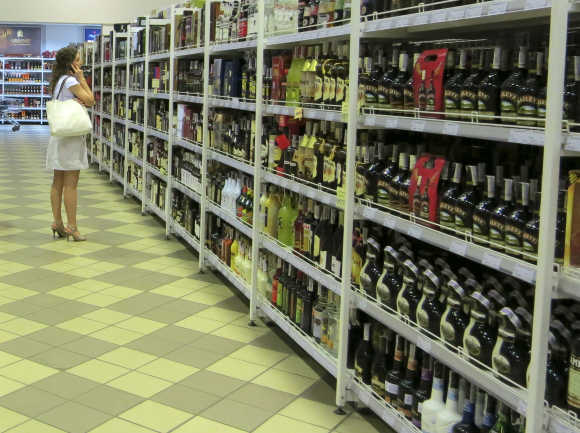 A shopper stands near bottles of alcohol at a supermarket in Kiev, Ukraine.