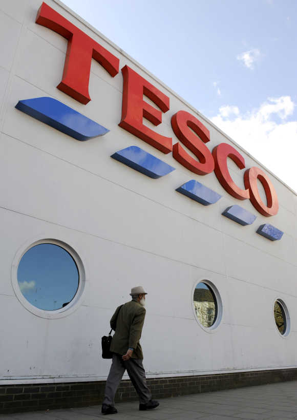 Man passes a branch of the Tesco supermarket in central London.