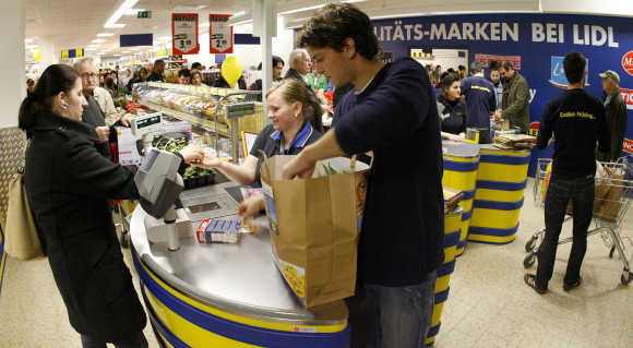 An employee packs the bag for a custumer at the cash desk of a Lidl supermarket in Zurich.