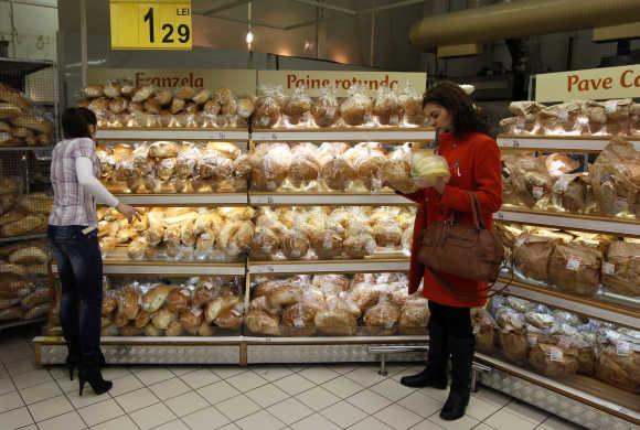 Women buy bread in a supermarket in Bucharest, Romania.