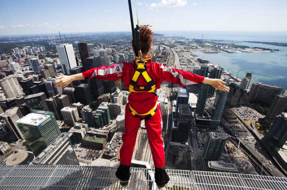 A reporter leans over the edge during the media preview for the 'EdgeWalk' on the CN Tower in Toronto.