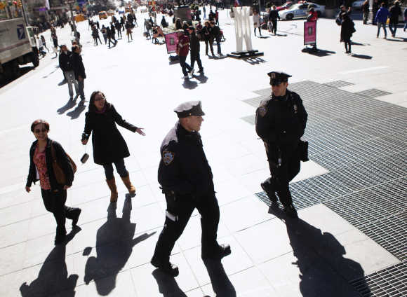 Two police officers walk amongst passing tourists in Times Square during a warm winter day in New York.