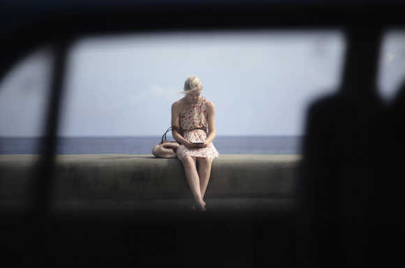 A tourist sits on Havana's seafront boulevard El Malecon, Cuba.
