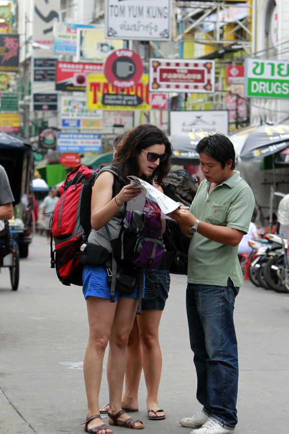 Tourists ask a 'tuk tuk' taxi driver for directions along Khao San Road in Bangkok.