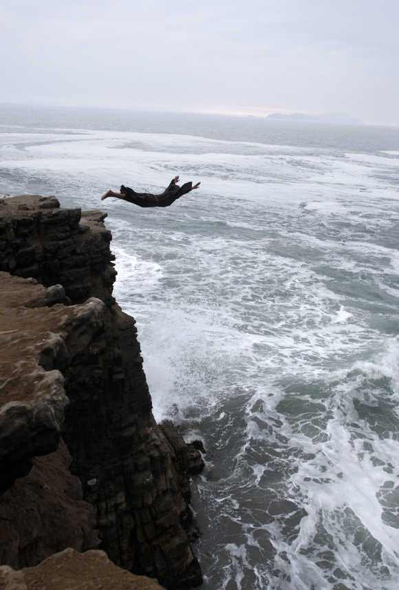 A man dressed as a friar jumps from a 10 metre (33ft) cliff in Lima, Peru.