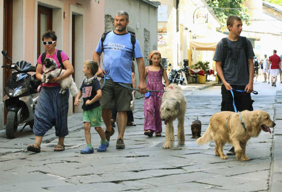 A family of Italian tourists walks their dogs in Croatia's northern Adriatic city of Pula, 270km south-west of Zagreb.